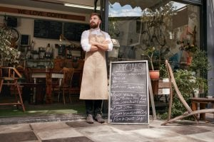 Full length shoot of a young waiter standing in door of a cafe. Young man with beard wearing an apron standing with her arms crossed and looking away.